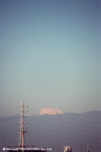 ビルの谷間の鉄塔の向こうに富士山の頭が見えている
