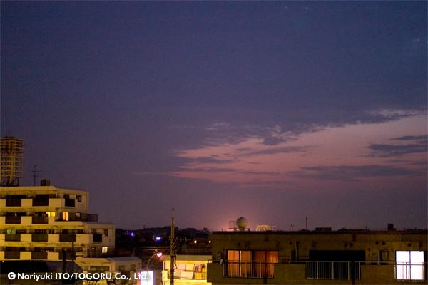 夕暮れ時、そらが紫から赤く染まっていて、街頭や建物の窓が明るく輝いている
