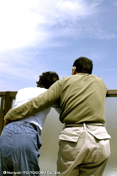 肩を組む両親の背中とその向こうに広がる青空